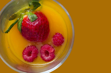 high view of non-alcoholic cocktail with strawberry and raspberry juice with orange background