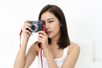 Portrait of a beautiful young Asian woman with a camera in white room, lifestyle