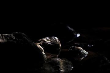Rocks in the stream dark black background (Selective Focus)
