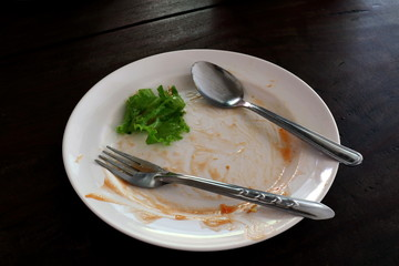 plate empty trash food and Leaves of green vegetables on a plate of rice, plate fork and spoon