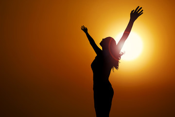 free and happy woman raises her arms to heaven