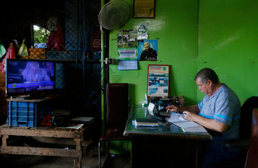 A man listens to a TV transmitting the Inter-American Commission on Human Right's final report on the repressive crackdown against protesters that began April 18 in Managua