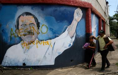 People walk in front of an image of Nicaragua's President Daniel Ortega in Managua