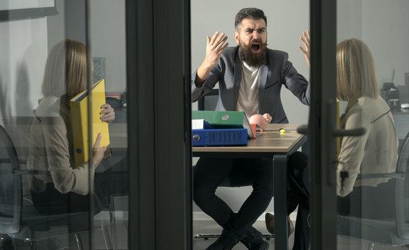 Angry irate boss yelling and shouting at secretary employee