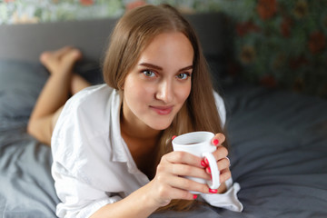 Attractive smiling european woman using laptop and drinking coffee while lying on her bed. Young woman drinking coffee at home in her bed, start, concept in the morning, early in the morning.