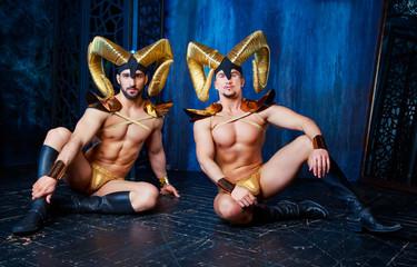 muscular handsome men  wearing big golden horns in the studio