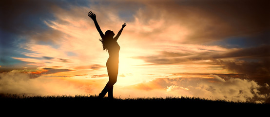 free and happy woman raises her arms at sunset