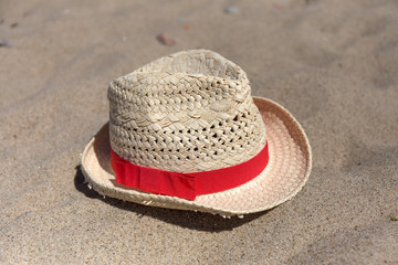 Wicker hat with red band laying on the sea sand