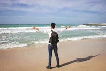 human stands and looks at the ocean