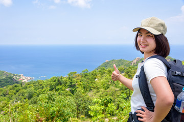 Women tourist with a backpack wear cap raise thumbs up for the beautiful nature landscape blue sea and sky from high scenic viewpoint at Koh Tao, Surat Thani, Thailand