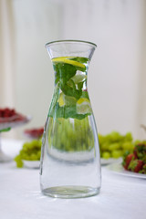 Soft focus photo of decanter with mint and lemon lemonade on table with fruits on bacground
