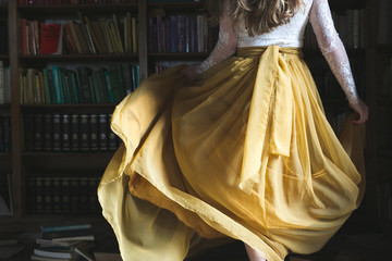 Gril in yellow dress in library