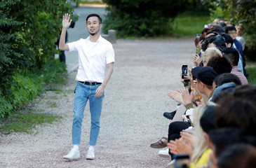 Designer Sean Suen appears at the end of his Spring/Summer 2019 collection show during Men's Fashion Week in Paris