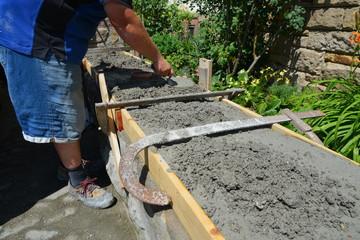 Mauersetzer rekonstruieren eine Gartenmauer aus buntem Natur-Sandstein fachmännisch: Glattstrich des Mauerabschlusses in der  Schalung, Hessen, Deutschland