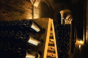 Pupitre and bottles inside an underground cellar for the production of traditional method sparkling wines in italy