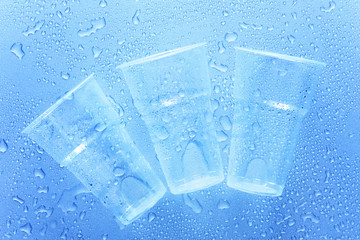 Three disposable plastic cup with water drops on a blue background