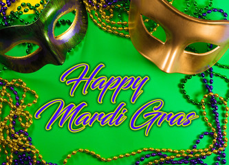 Wall Mural - Two Mardi Gras mask with colorful beads on a green background with greeting