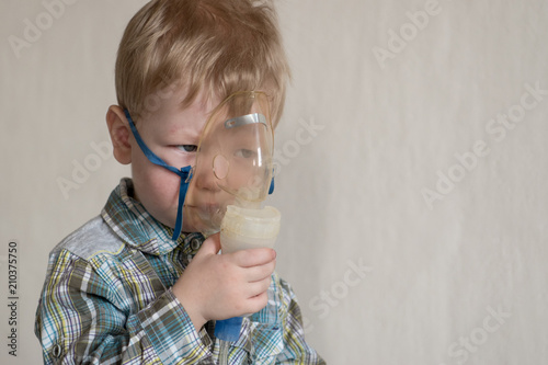Caucasian blonde boy inhales couples containing medication to stop