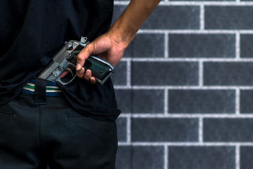 Robber or gangster, thief, Stress man holding gun in hand ready to shoot with grey brick wall Criminal concept.