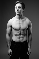 Studio shot of young muscular handsome man shirtless in black an