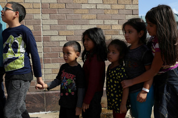 Children form a line as undocumented immigrant families are released from detention at a bus depot in McAllen