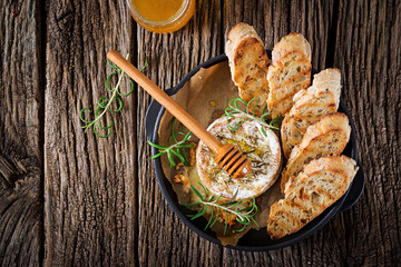 Baked cheese Camembert with rosemary and honey. Tasty food. Top view. Flat lay