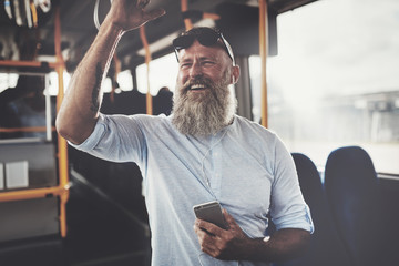 Smiling mature man riding a bus listening to music Wall mural