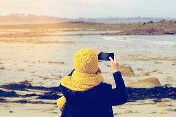 Eine Frau mit einem Smartphone fotografiert am Strand