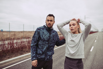 Young couple in sportswear standing together on a country road