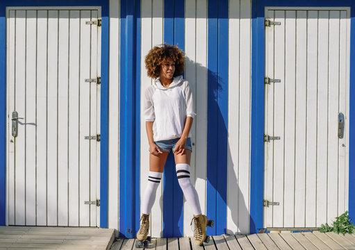 Young black woman on roller skates near a beach hut.