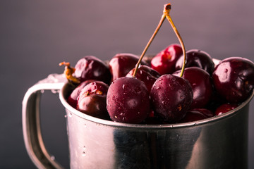 Frozen cherries on a gradient red in a metal cup. Close up. Toned, dark moody. Minimalism concept