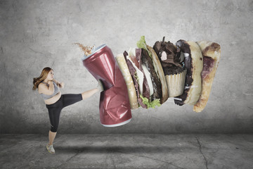 Fat woman kicking unhealthy food and drink