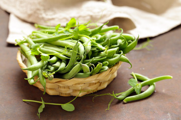 fresh organic pods green peas on a wooden table