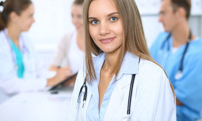 Happy doctor woman  with medical staff at the background in hospital office
