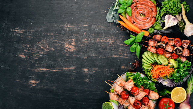 Assortment of baked barbecue meat. Sausages, skewers, fresh vegetables. Tomatoes, onions, garlic. On a wooden background. Copy space.