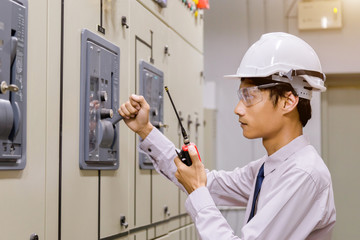 Control Room Engineer. Power Plant Control Panel. Engineer standing in front of the control panel in the control room and write the results of the measurements and check system ready .