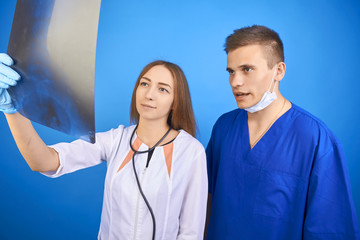 two doctors are looking at an x-ray picture.