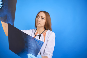 girl doctor looks at x-ray picture.