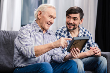 Positive father and son looking at a photo frame