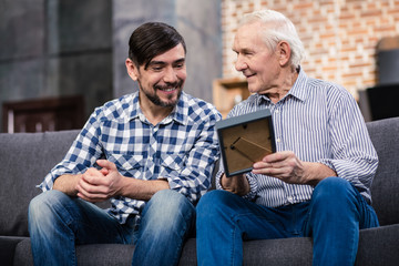 Positive man with his retired father holding a photo frame