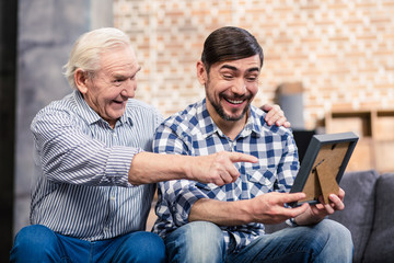 Joyful father and son looking at a photo frame