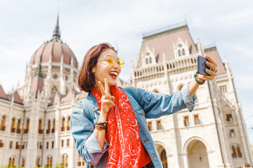 Happy young asian woman tourist making selfie photo by using her smartphone standing in front of the old bridge in Budapest city with view of the Parliament Building