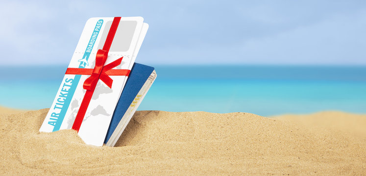 Air tickets as  gift with red ribbon and bow. Passport and air tickets in the sand on the beach of the sea