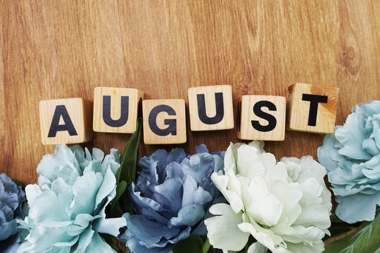 august alphabet letter wooden cube with space copy on wooden background and flower decoration