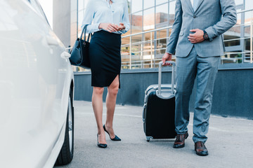 partial view of business people with luggage walking to car on parking