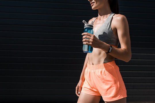 cropped view of sportswoman with fitness tracker holding bottle of water