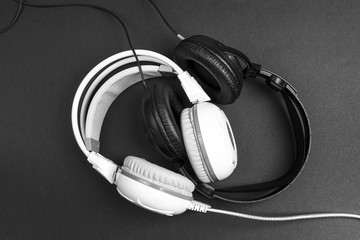 Black and white headphones on black backgrounds. The musical yin-yang.