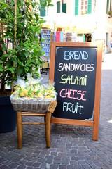 Schwarze Holztafel mit angebotenen Waren vor einem Lebensmittelgeschäft