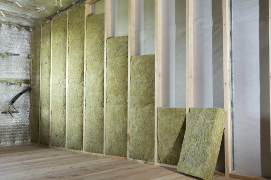 Wooden frame for future walls insulated with rock wool and fiberglass insulation staff for cold barrier. Comfortable warm home, economy, construction and renovation concept.