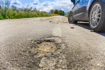 bad road cracked and damaged. car in blurred background